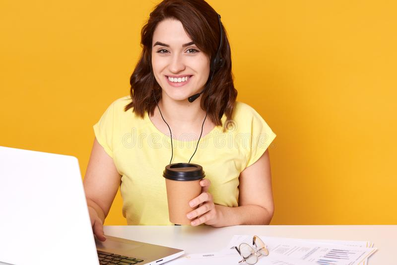 Φωτογραφία της όμορφης νέας τοποθέτησης χειριστών τηλεφωνικών κέντρων στο κίτρινο κλίμα καθμένος στο άσπρο γραφείο με τα ακουστικ στοκ εικόνα