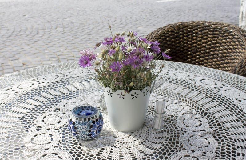 Φωτογραφία του άνετου πίνακα καφέδων στην οδό πετρών επίστρωσης το ηλιόλουστο θερινό πρωί με τα όμορφα λουλούδια στο τραπεζομάντι στοκ εικόνα