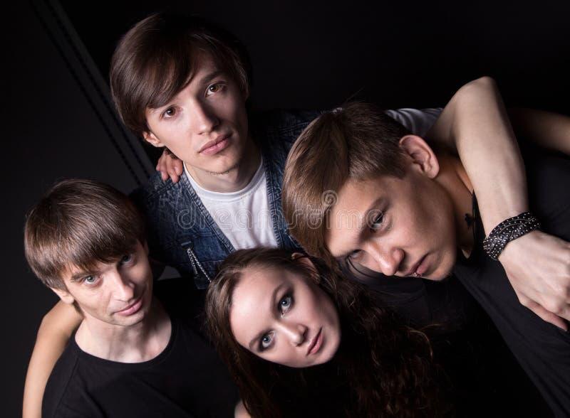 Φωτογραφία του αγκαλιάσματος τεσσάρων φίλων από την κορυφή στοκ εικόνες