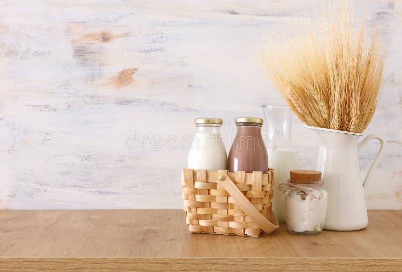 Φωτογραφία του γάλακτος και της σοκολάτας δίπλα στο σίτο πέρα από τον ξύλινο πίνακα και το άσπρο υπόβαθρο Σύμβολα των εβραϊκών δι στοκ εικόνα με δικαίωμα ελεύθερης χρήσης