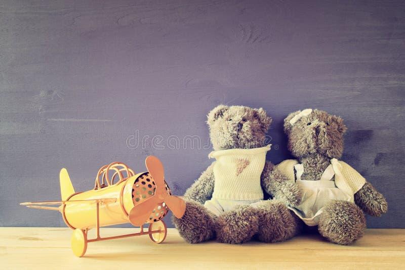 Φωτογραφία του εκλεκτής ποιότητας αεροπλάνου παιχνιδιών και ζεύγος των χαριτωμένων teddy αρκούδων στοκ εικόνες