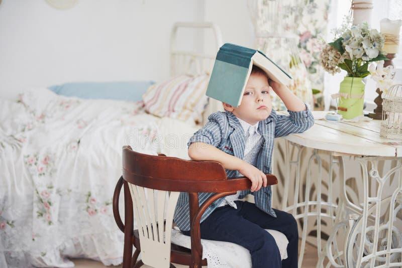 Φωτογραφία του επιμελούς μαθητή με το βιβλίο στο κεφάλι του που κάνει την εργασία Ο μαθητής είναι κουρασμένος να κάνει την εργασί στοκ φωτογραφία με δικαίωμα ελεύθερης χρήσης