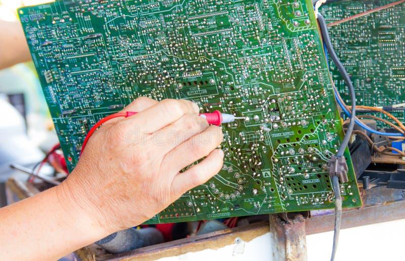 Φωτογραφία του επισκευαστή που εξετάζει το κύκλωμα TV στοκ εικόνες