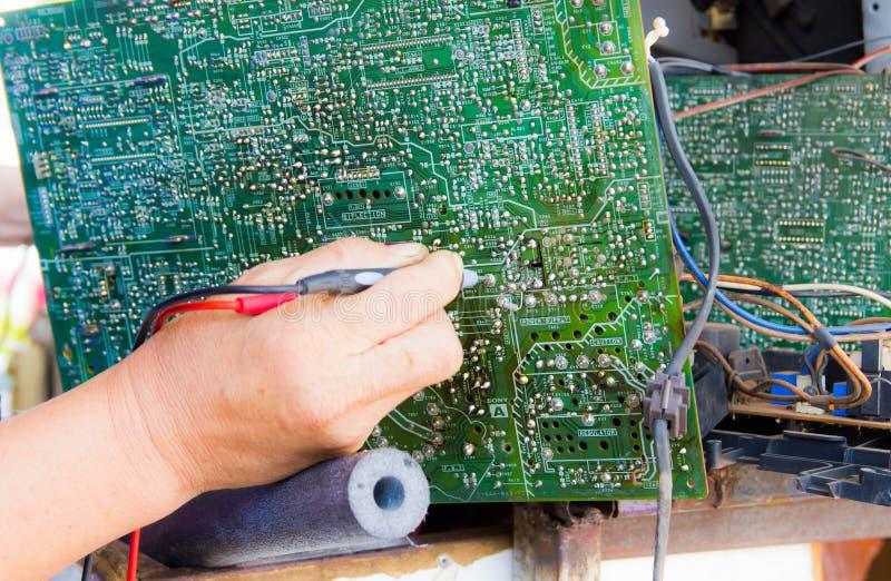 Φωτογραφία του επισκευαστή που εξετάζει το κύκλωμα TV στοκ φωτογραφία