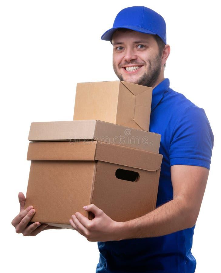 Φωτογραφία του ευτυχούς αρσενικού αγγελιαφόρου με τα κουτιά από χαρτόνι στοκ εικόνες