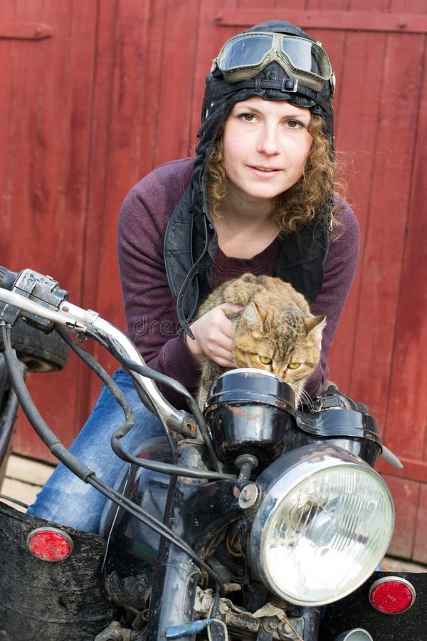 Φωτογραφία του κοριτσιού σε μια εκλεκτής ποιότητας μοτοσικλέτα στην πειραματική ΚΑΠ με τη γάτα στοκ εικόνα