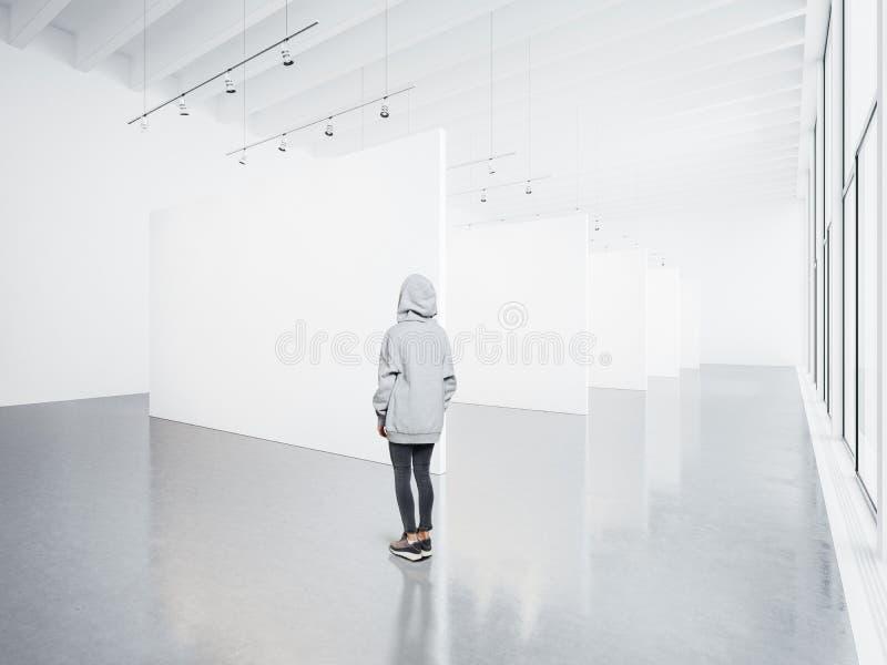 Φωτογραφία του κοριτσιού στην κενή σύγχρονη στοά που εξετάζει τον κενό άσπρο καμβά Μεγάλα παράθυρα, επίκεντρα, τσιμεντένιο πάτωμα στοκ εικόνα