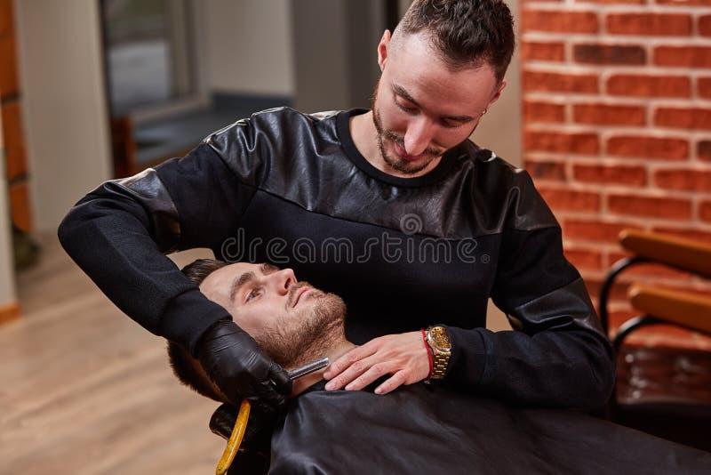 Φωτογραφία του κυρίου ενώ κάνει τη διόρθωση γενειάδων για τον πελάτη στο σαλόνι barbershop στοκ εικόνες με δικαίωμα ελεύθερης χρήσης