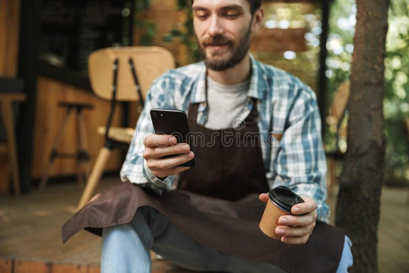 Φωτογραφία του χαρούμενου ατόμου σερβιτόρων που χρησιμοποιεί το smartphone λειτουργώντας στον καφέ ή το καφέ υπαίθριο στοκ φωτογραφία