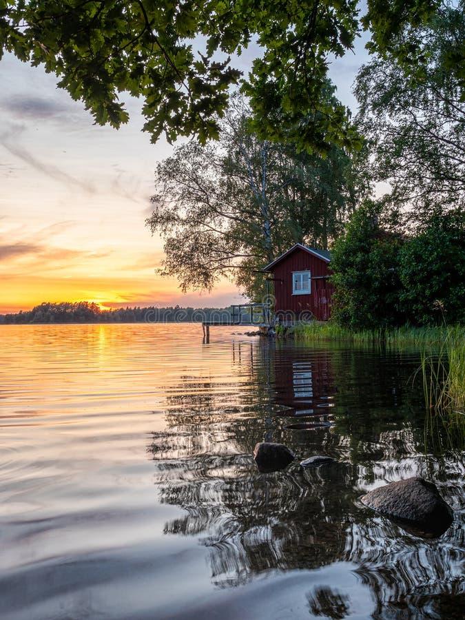 Φωτογραφία του Lakeside Sunset με δέντρα, σκανδιναβικό ξύλινο σπίτι και γαλάζιο ουρανό στοκ φωτογραφία με δικαίωμα ελεύθερης χρήσης