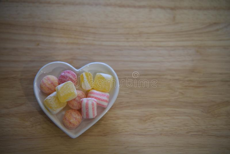 Φωτογραφία τροφίμων για τους βαλεντίνους με το άσπρο πιάτο μορφής καρδιών αγάπης που γεμίζουν με τα γλυκά ζάχαρης καραμελών στα κ στοκ εικόνα με δικαίωμα ελεύθερης χρήσης