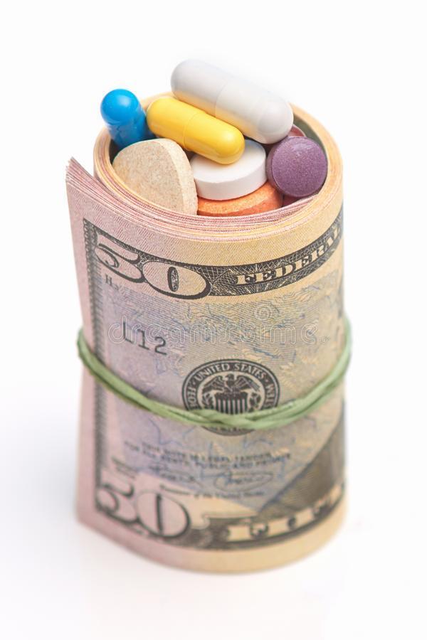Φωτογραφία των κυλημένων επάνω δολαρίων και πολλών χαπιών μέσα χρήματα φαρμάκων από κοινού Τιμή ιατρικής Βοήθεια ιατρικής Δωροδοκ στοκ εικόνα