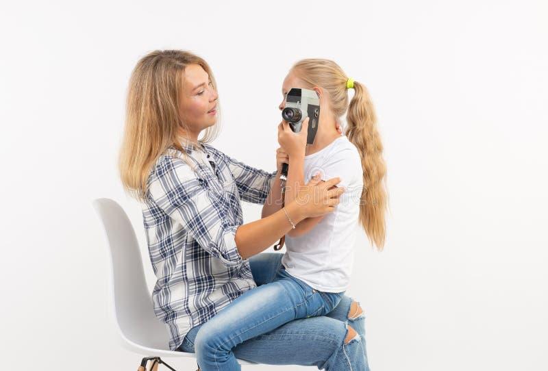 Φωτογραφία, φωτογράφος και αναδρομική έννοια καμερών - νέα γυναίκα και η κόρη εφήβων της που χρησιμοποιούν την εκλεκτής ποιότητας στοκ εικόνα με δικαίωμα ελεύθερης χρήσης