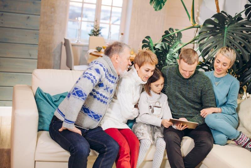 Φωτογραφίες προσοχής πολυμελών οικογενειών Frinedly από την ταμπλέτα στοκ εικόνες