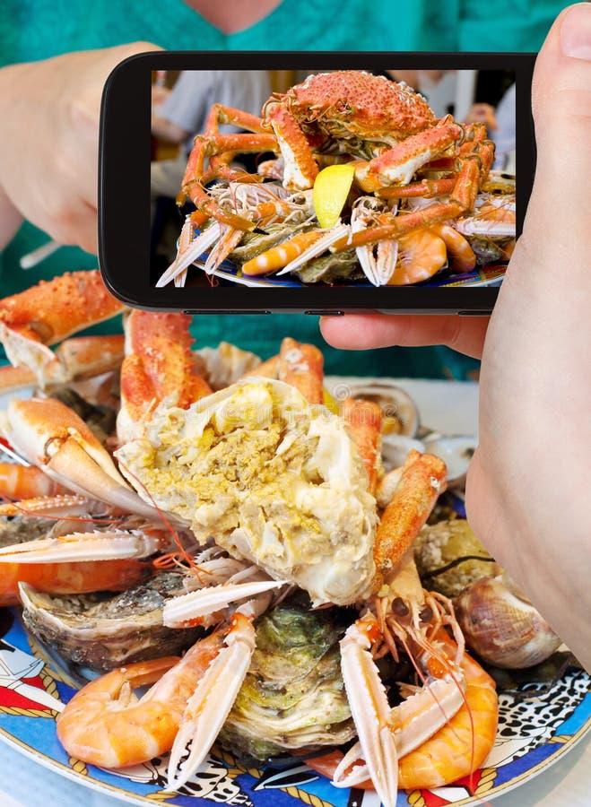 Φωτογραφίες τουριστών του πιάτου θαλασσινών με το καβούρι, γαρίδες, γαρίδες στοκ φωτογραφίες