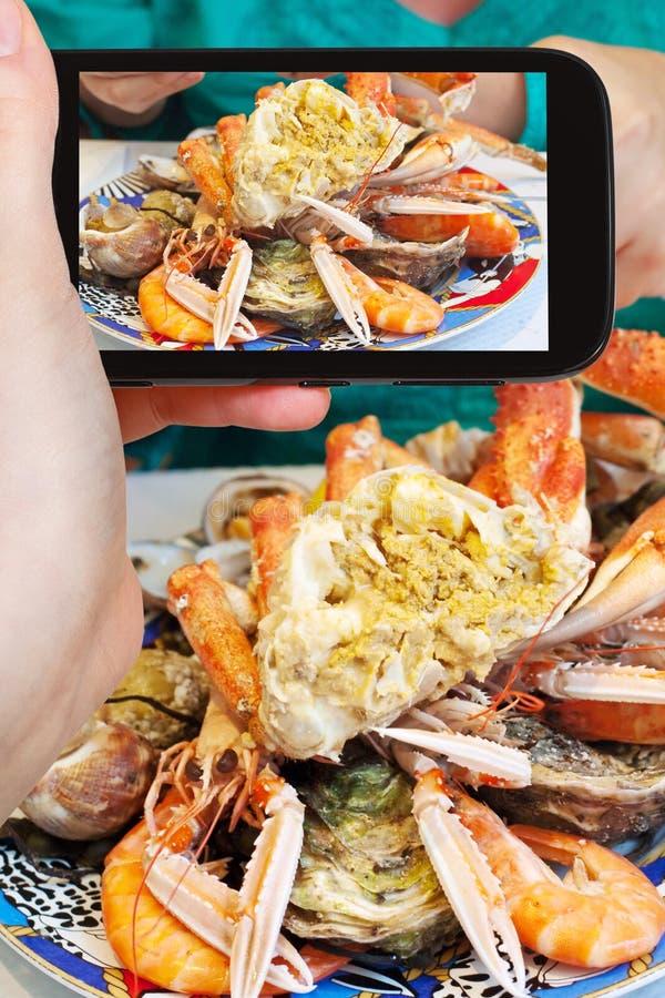 Φωτογραφίες τουριστών του πιάτου με το καβούρι και τα θαλασσινά στοκ εικόνα με δικαίωμα ελεύθερης χρήσης
