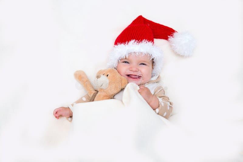 Φωτογραφίες του χαμογελώντας νέου μωρού σε ένα καπέλο Άγιου Βασίλη στοκ εικόνα με δικαίωμα ελεύθερης χρήσης