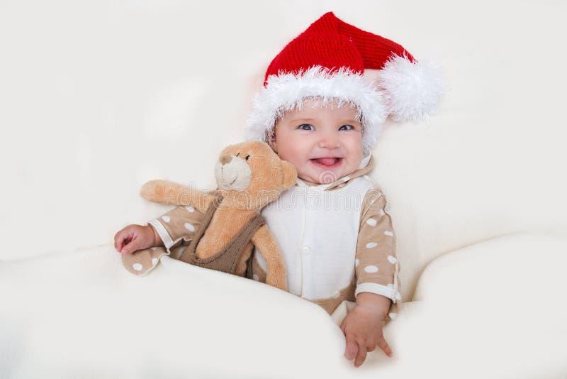 Φωτογραφίες του χαμογελώντας νέου μωρού σε ένα καπέλο Άγιου Βασίλη στοκ φωτογραφίες
