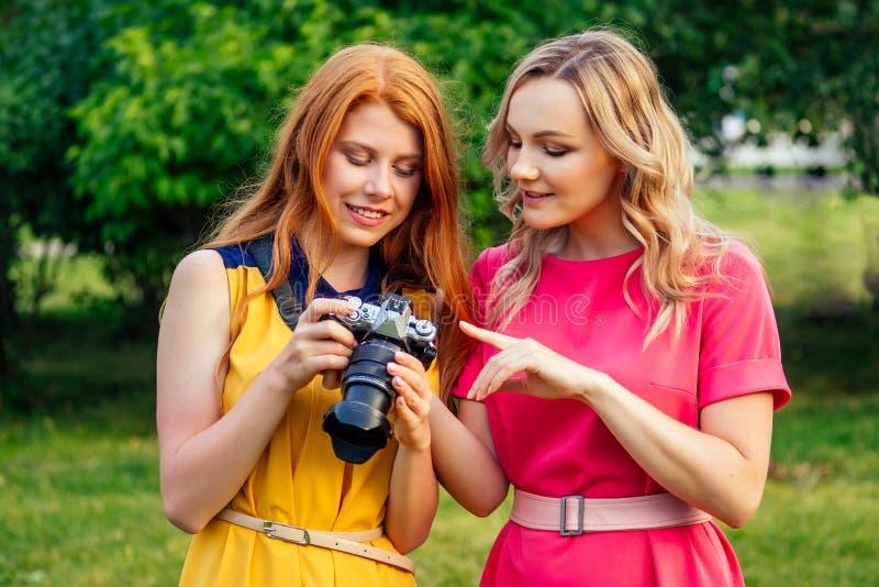 Φωτοσυνοδός όμορφη κοκκινομάλλα κοπέλα με κίτρινο φόρεμα και ξανθιά γυναίκα με ροζ φόρεμα στοκ φωτογραφίες με δικαίωμα ελεύθερης χρήσης