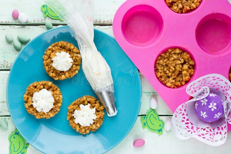 Φωλιές μπισκότων Πάσχας με την κτυπημένη κρέμα και τη μίνι καραμέλα αυγών στοκ εικόνες με δικαίωμα ελεύθερης χρήσης