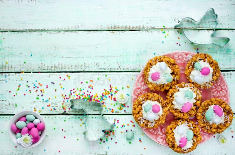 Φωλιές μπισκότων Πάσχας με την κτυπημένη κρέμα και τη μίνι καραμέλα αυγών στοκ εικόνες