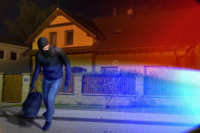 Φω'τα αστυνομίας και καλυμμένος δραπέτης διαρρήκτης με balaclava και blac στοκ εικόνα