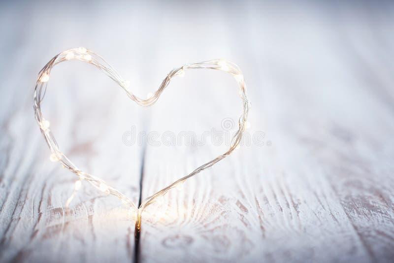Φω'τα γιρλαντών με μορφή μιας καρδιάς σε έναν άσπρο ξύλινο πίνακα Η έννοια της αγάπης και της ημέρας βαλεντίνων ` s στοκ φωτογραφίες με δικαίωμα ελεύθερης χρήσης
