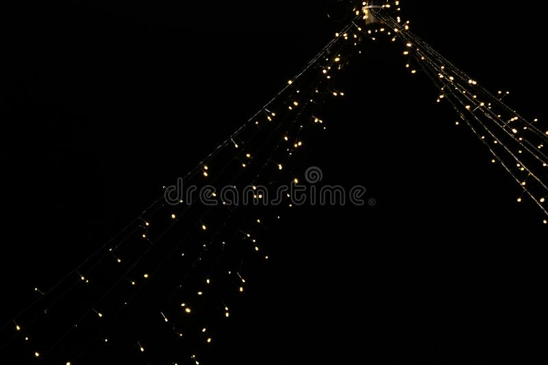 Φω'τα με τις κίτρινες λάμπες φωτός που κρεμούν από το ανώτατο όριο με το βαθύ μαύρο υπόβαθρο με το διάστημα για το κείμενο στοκ εικόνες με δικαίωμα ελεύθερης χρήσης