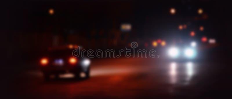 Φω'τα νυχτών της μεγάλης πόλης, η θολωμένη λεωφόρος νύχτας με τους φωτεινούς σηματοδότες bokeh και τους προβολείς του πλησιάζοντα στοκ φωτογραφία με δικαίωμα ελεύθερης χρήσης