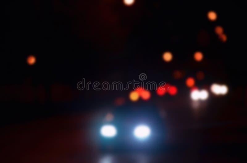 Φω'τα νυχτών της μεγάλης πόλης, η θολωμένη λεωφόρος νύχτας με τους φωτεινούς σηματοδότες bokeh και τους προβολείς του πλησιάζοντα στοκ εικόνες