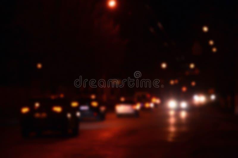 Φω'τα νυχτών της μεγάλης πόλης, η θολωμένη λεωφόρος νύχτας με τους φωτεινούς σηματοδότες bokeh και τους προβολείς του πλησιάζοντα στοκ εικόνα με δικαίωμα ελεύθερης χρήσης