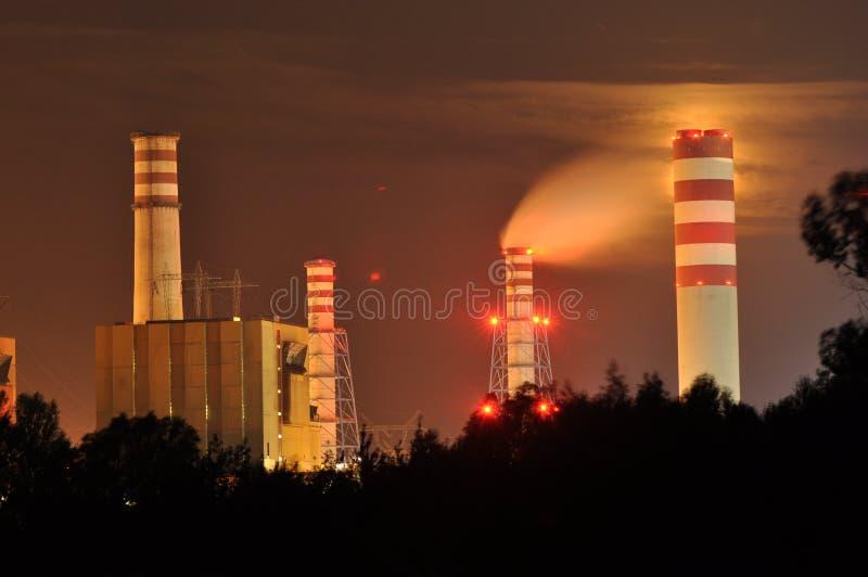 Φω'τα δύναμης που φωτίζονται τη νύχτα Καπνοδόχοι που προωθούν τον καπνό Γερανοί, που επεκτείνουν το ηλεκτρόνιο Παραγωγή θερμότητα στοκ εικόνες