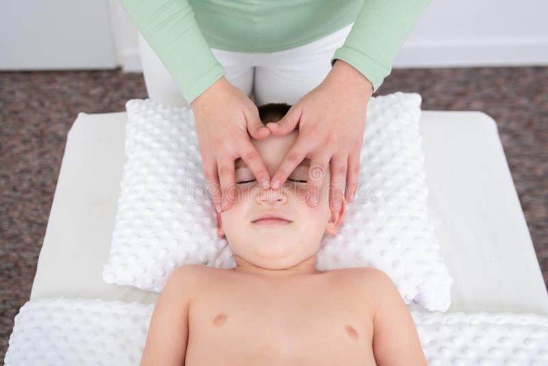Φόντο έννοιας μασάζ για παιδιά Γυναίκα θεραπευτής κάνει μασάζ σε νεαρό αγόρι Επάνω όψη στοκ εικόνα