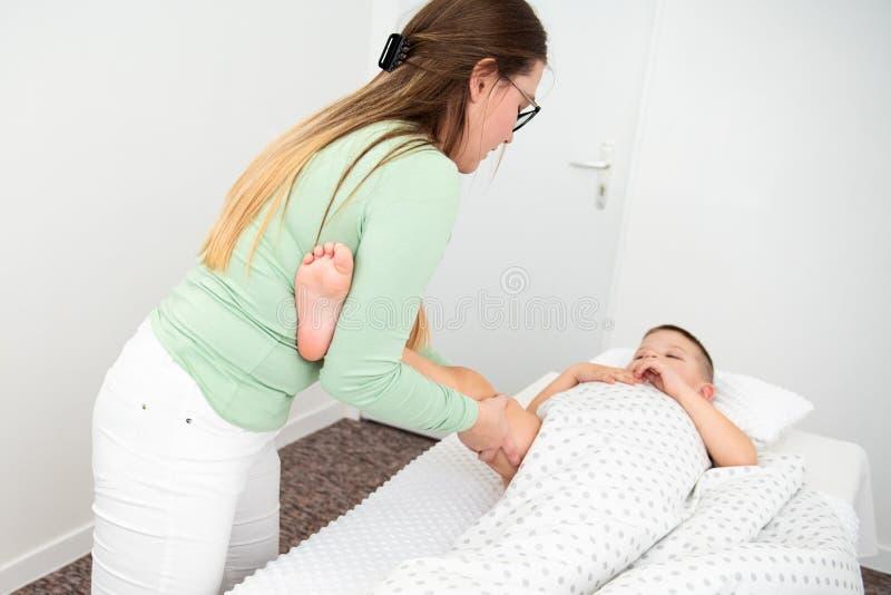 Φόντο έννοιας μασάζ για παιδιά Νεαρές γυναίκες θεραπεύτριες μασάζ που κάνουν μασάζ στα πόδια ενός 6χρονου αγοριού Φυσική θεραπεία στοκ φωτογραφία με δικαίωμα ελεύθερης χρήσης