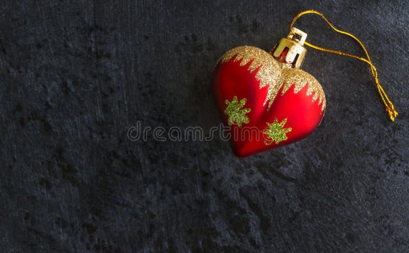 Φόντο της Πρωτοχρονιάς με κόκκινο παιχνίδι σε σκούρο φόντο στοκ εικόνες