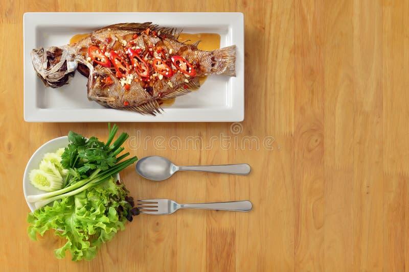 Φόντο φαγητού ταϊλανδέζικου στιλ, τηγανητό ολόκληρο θαλασσινό με σκόρδο και τσίλι σε σάλτσα ψαριού σε ξύλινο τραπέζι στοκ εικόνες
