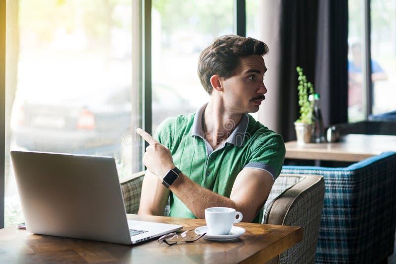 Φύγε από εδώ. Νεαρός δυσαρεστημένος επιχειρηματίας με πράσινο μπλουζάκι που κάθεται και εργάζεται στο φορητό υπολογιστή και δείχν στοκ εικόνα με δικαίωμα ελεύθερης χρήσης