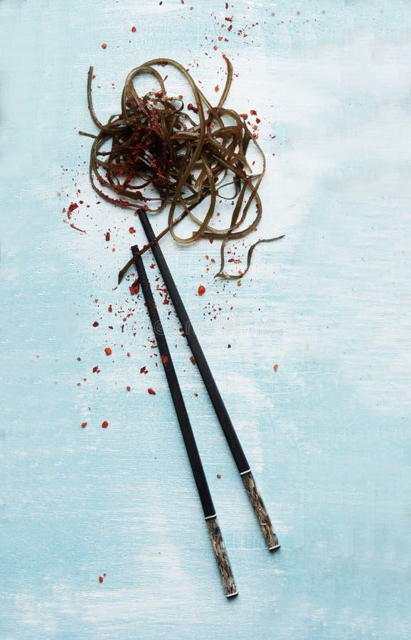 Φύκι και chopsticks σε ένα μπλε υπόβαθρο στοκ φωτογραφία