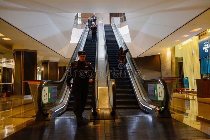 Φύλακας που περπατεί από τις υπόγειες κυλιόμενες σκάλες στοκ εικόνες