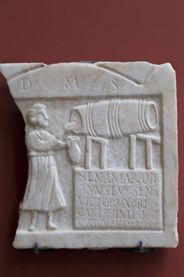 Φύλακας ταβερνών που τρυπά το κρασί από ένα βαρέλι, ρωμαϊκή ανακούφιση στοκ εικόνες