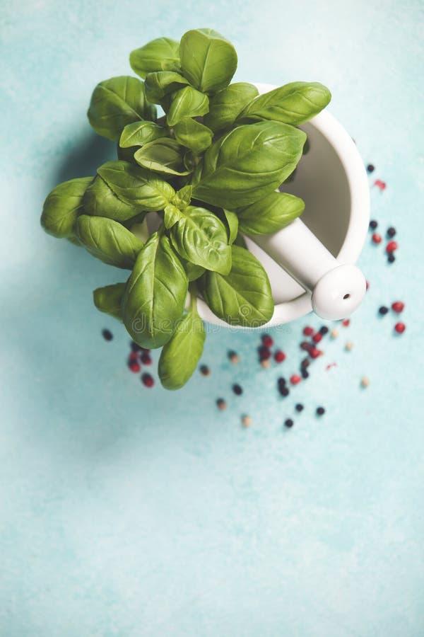 Φύλλα βασιλικού με το κονίαμα και το γουδοχέρι στοκ εικόνες
