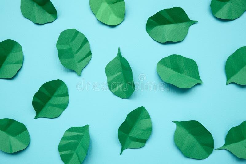 Φύλλα σπανακιού και arugula που γίνονται από το έγγραφο για το μπλε υπόβαθρο Έννοια ελάχιστης, δημιουργικής, vegan, υγιούς ή τέχν στοκ φωτογραφίες