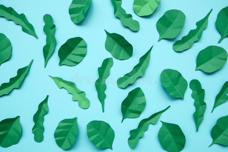 Φύλλα σπανακιού και arugula που γίνονται από το έγγραφο για το μπλε υπόβαθρο Έννοια ελάχιστης, δημιουργικής, vegan, υγιούς ή τέχν στοκ εικόνα με δικαίωμα ελεύθερης χρήσης