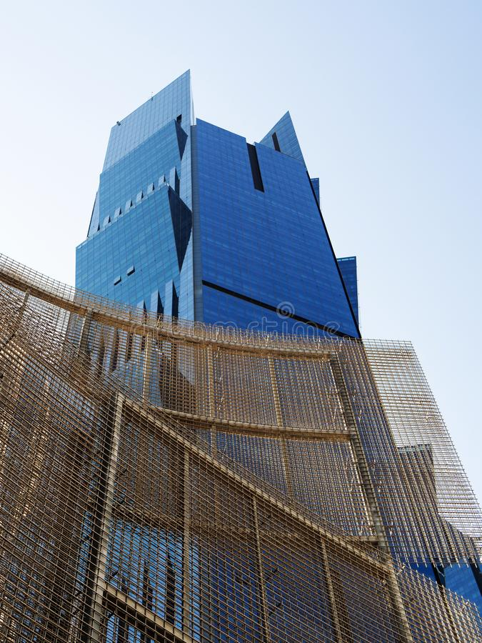 Φύλλα του ενωμένου στενά πλέγματος καλωδίων για το σύγχρονο σκελετό οικοδόμησης με τον ουρανοξύστη στο υπόβαθρο, κατώτατη άποψη,  στοκ φωτογραφία με δικαίωμα ελεύθερης χρήσης