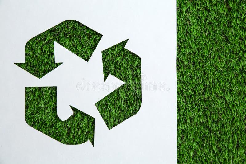 Φύλλο του εγγράφου με το σύμβολο ανακύκλωσης διακοπής στη χλόη, τοπ άποψη Διάστημα για το κείμενο απεικόνιση αποθεμάτων