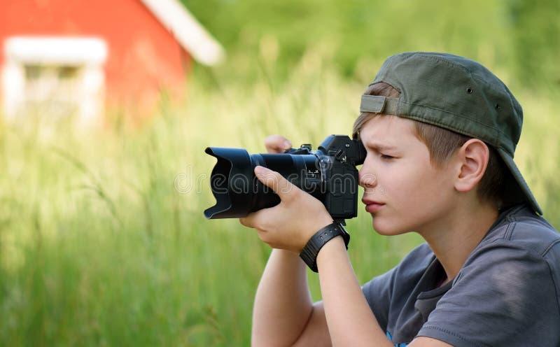 Φύση πυροβολισμού αγοριών με τη κάμερα SLR στοκ εικόνες