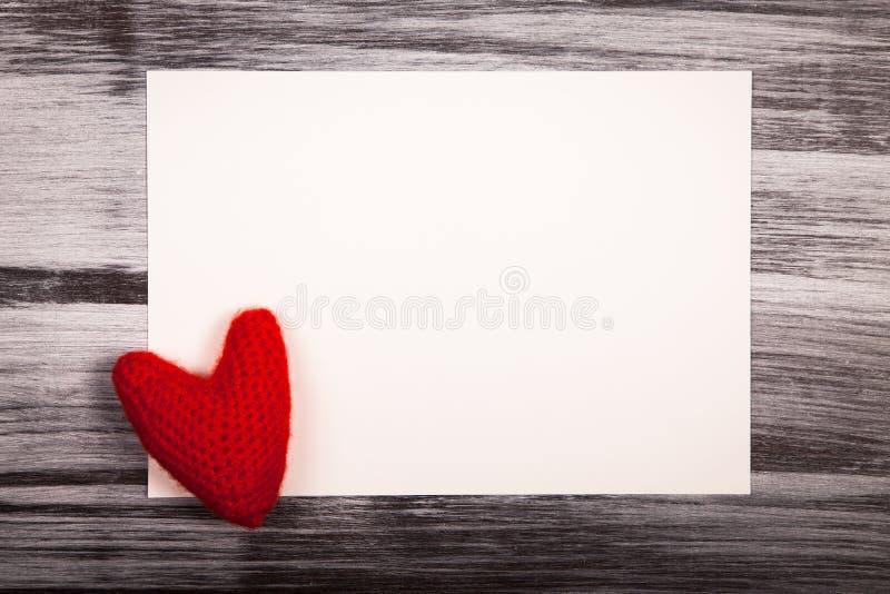 Φύλλο και πλεκτή κόκκινη καρδιά, ημέρα του βαλεντίνου, καφετιά ξύλινη ΤΣΕ στοκ φωτογραφία με δικαίωμα ελεύθερης χρήσης