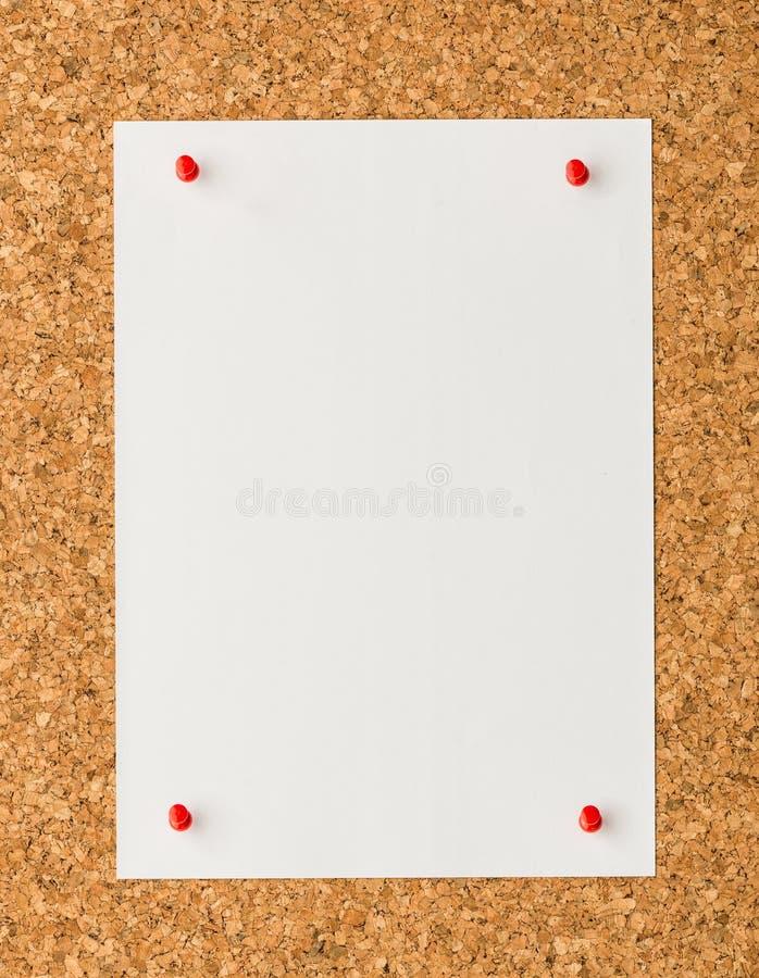 Φύλλο σημειώσεων της Λευκής Βίβλου με την κόκκινη καρφίτσα ώθησης στον πίνακα φελλού στοκ εικόνες