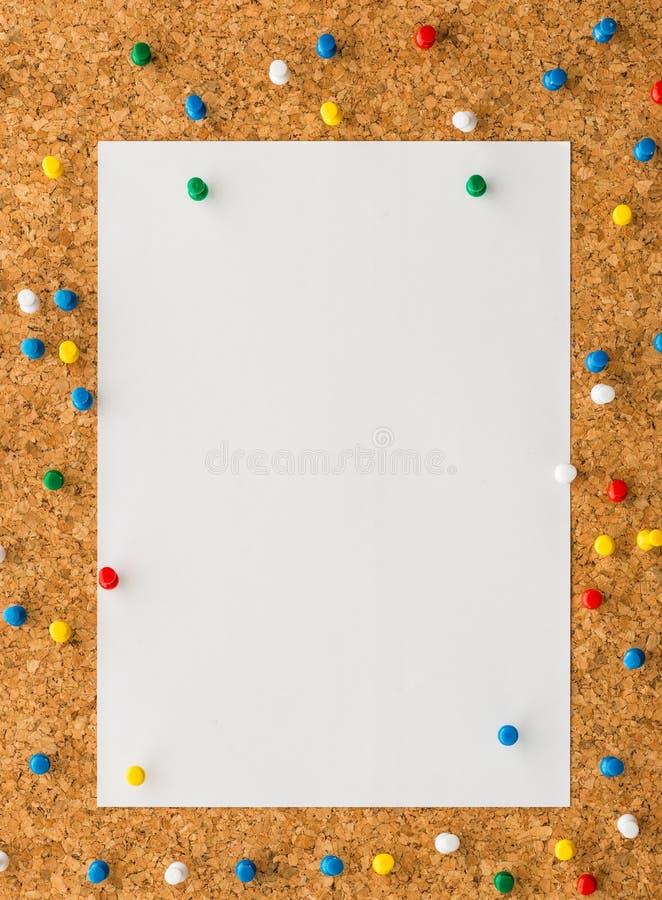 Φύλλο σημειώσεων της Λευκής Βίβλου με την πολύχρωμη καρφίτσα ώθησης στον πίνακα φελλού στοκ φωτογραφίες