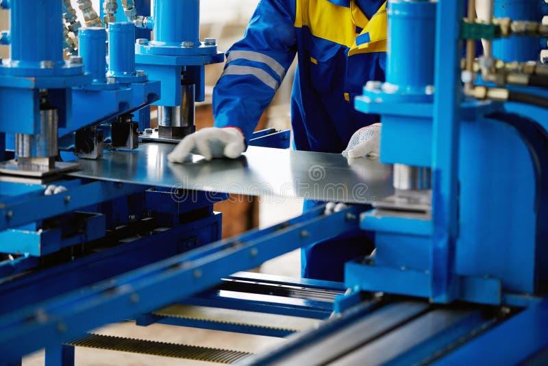Φύλλο του μετάλλου και χέρια του εργαζομένου στοκ εικόνα